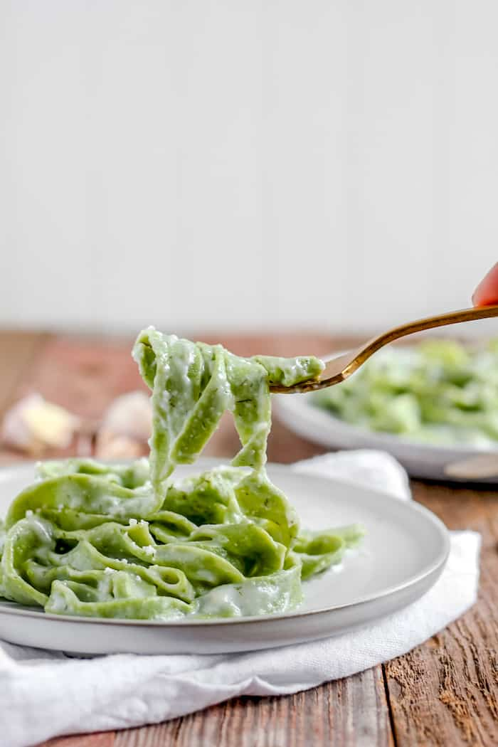 A plate of homemade spinach pasta with garlic dill sauce
